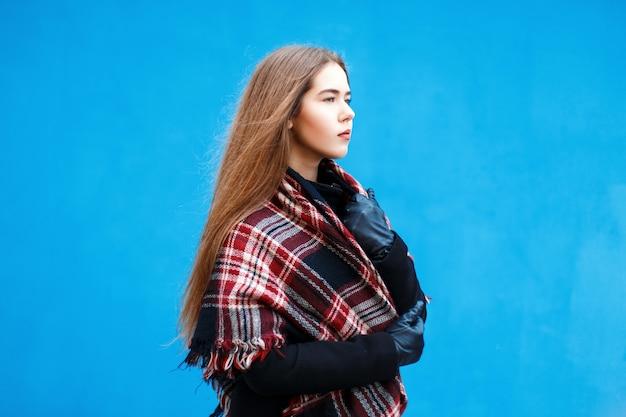 Bella giovane donna con una sciarpa e un cappotto vicino al muro blu