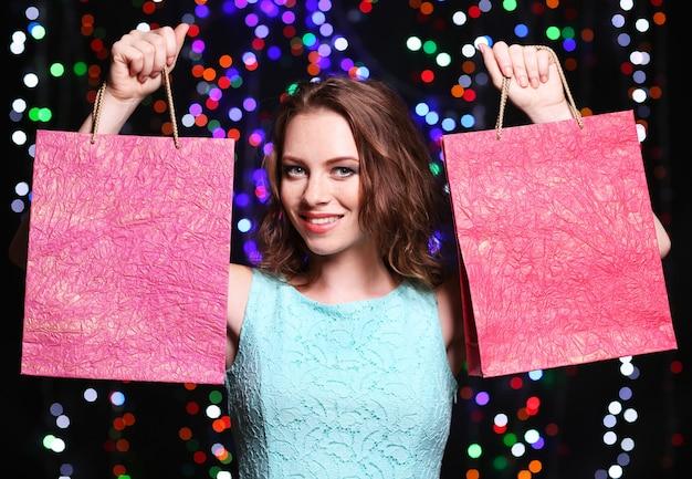 Bella giovane donna con le borse della spesa su sfondo di luci intense