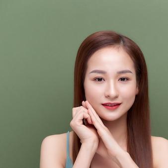 Bella giovane donna con pelle setosa dopo il trattamento termale su sfondo colorato