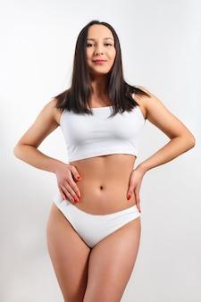 Bella giovane donna con una figura snella in biancheria intima bianca su sfondo bianco