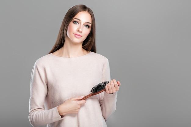 La bella giovane donna con capelli naturali lunghi lisci tiene la spazzola per capelli. copia spazio