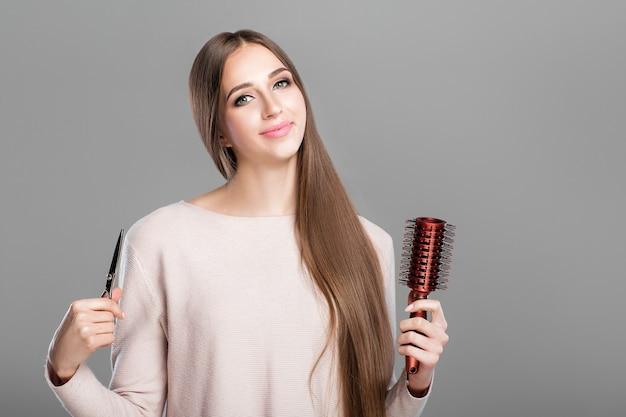La bella giovane donna con capelli naturali lunghi e lisci tiene la spazzola per capelli e le forbici