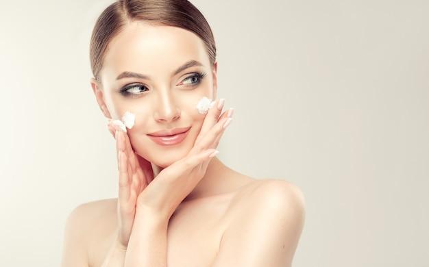Bella, giovane donna con macchie di crema cosmetica sulla pelle ben curata
