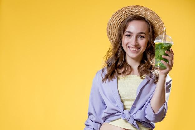 Bella giovane donna con cappello di paglia che tiene cocktail in tazza di plastica su sfondo giallo yellow