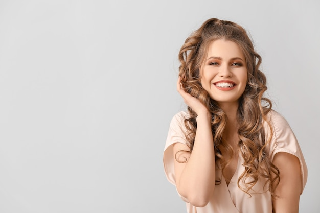 Bella giovane donna con acconciatura alla moda sulla parete grigia con lo spazio della copia copy