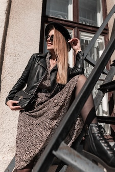 Bella giovane donna con occhiali da sole e un cappello in un abito alla moda con un'elegante giacca di pelle nera in posa su una scala di metallo alla luce del sole