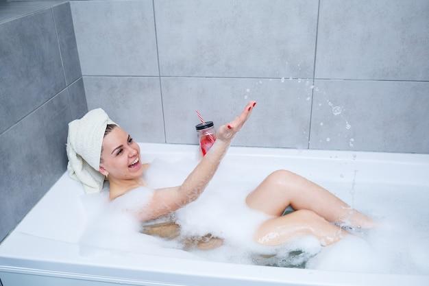 La bella giovane donna con un asciugamano sulla sua testa che beve un cocktail fa un bagno a casa. rilassati dopo una dura giornata. la spa è una procedura rilassante.