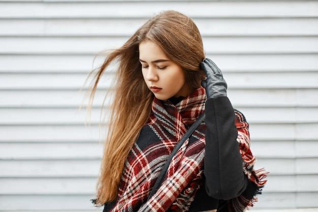 Bella giovane donna con una sciarpa vintage alla moda vicino a una parete in legno