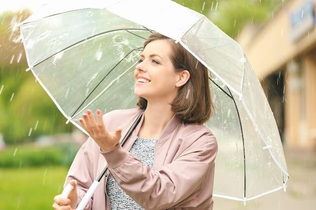 Bella giovane donna con l'ombrello all'aperto in una giornata piovosa