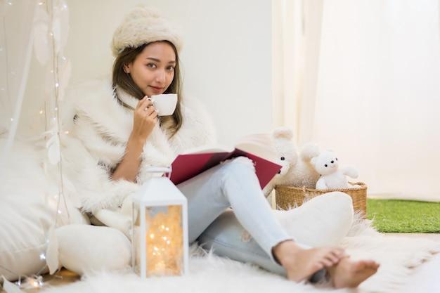 Bella giovane donna con cappello di pelliccia bianca e maglione leggere il libro e bere caffè o tè caldo in casa in inverno. la ragazza sorridente celebra le vacanze di natale a casa.