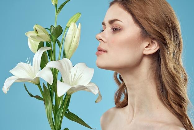 Bella giovane donna con fiore di giglio bianco in posa in studio su sfondo blu, immagine tenera romantica