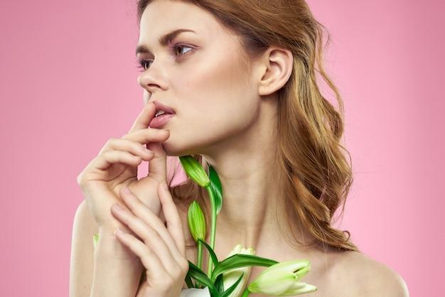 Bella giovane donna con il fiore del giglio bianco che posa nello studio sull'immagine tenera rosa e romantica