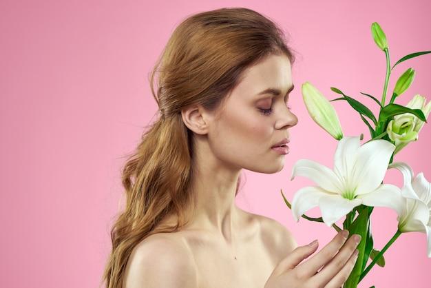 Bella giovane donna con il fiore del giglio bianco che posa nello studio su uno spazio rosa, immagine tenera romantica