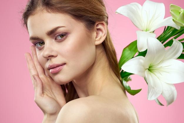Bella giovane donna con la posa bianca del fiore del giglio