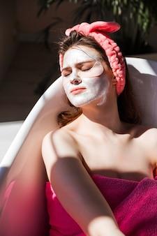 Una bellissima giovane donna con una maschera bianca sul viso posa in una vasca da bagno in ceramica bianca