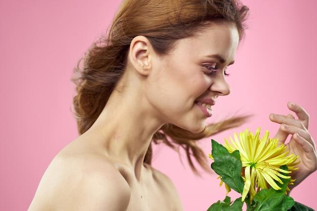 Bella giovane donna con una posa gialla del fiore