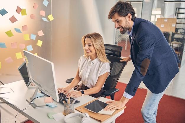 Bella giovane donna che lavora su un pc desktop e sorride mentre un uomo gioioso in piedi accanto a lei