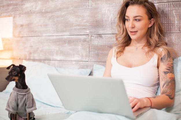 Bella giovane donna che lavora fino a tardi sul suo computer portatile che indossa un pigiama vicino al suo cagnolino.