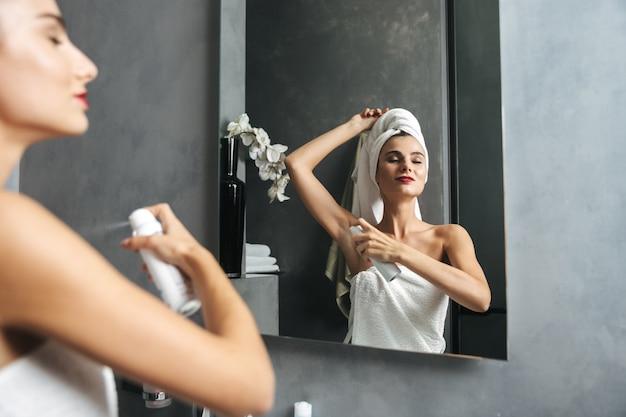 Bella giovane donna avvolta in un asciugamano da bagno in piedi in bagno