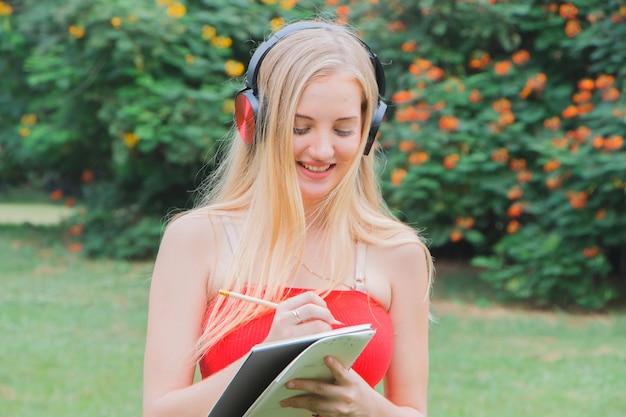 Bella giovane donna che scrive con una nota al parco?