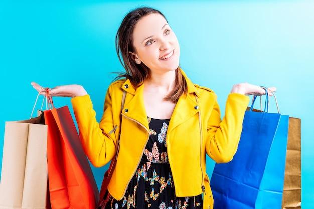 Bella giovane donna in giacca gialla su sfondo blu che tiene le borse della spesa colorate. lei shopaholic concetto. fine settimana di acquisti. saldi