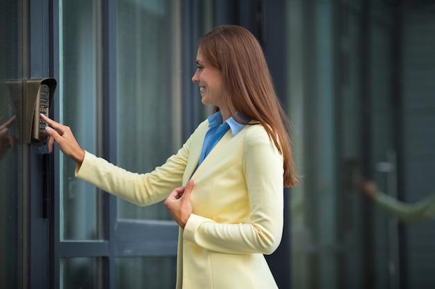Bella giovane donna in una giacca gialla suona il citofono