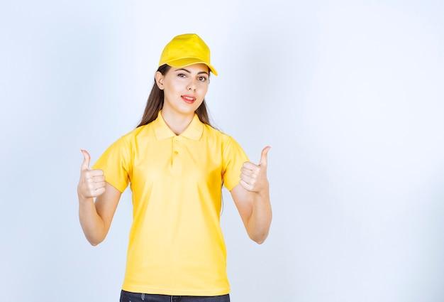 Bella giovane donna in abito giallo che dà segni su sfondo bianco.