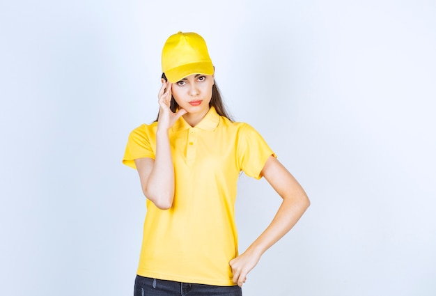 Bella giovane donna in maglietta gialla e berretto guardando in posa su sfondo bianco.