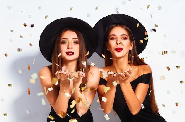 Belle giovani donne vestite come una strega per la festa di halloween