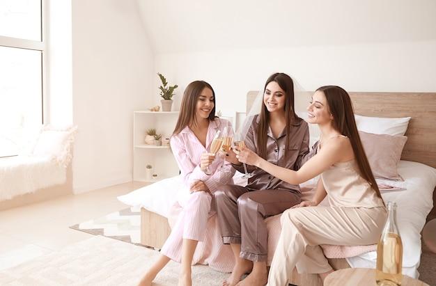 Belle giovani donne che bevono champagne durante la festa di addio al nubilato