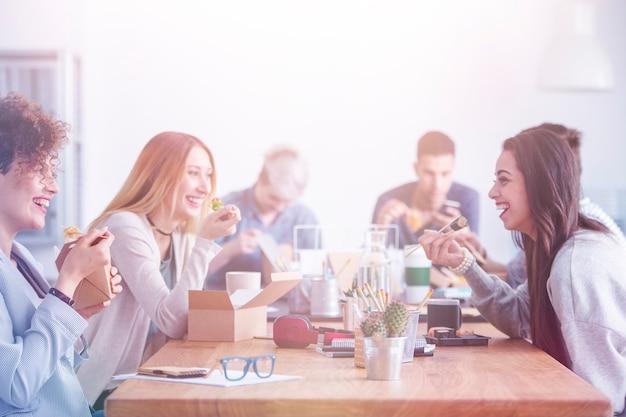 Belle giovani donne che fanno pausa pranzo in un ufficio di un'agenzia pubblicitaria