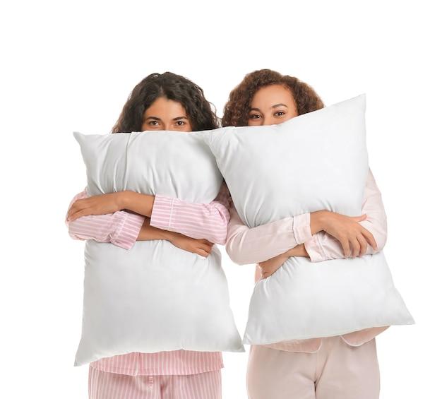 Belle giovani donne in pigiama e con cuscini isolati