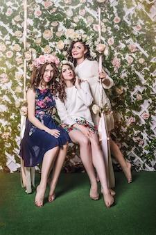 Belle giovani donne sorridenti che oscillano felicemente su un'altalena tra i fiori in ghirlande