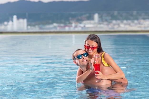 Belle giovani donne e cocktail beventi dell'uomo alla moda sulla spiaggia. buona vacanza luna di miele in paradiso. concetto attivo della piscina di svago delle giovani coppie