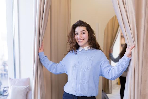 Belle giovani donne che provano i vestiti in un negozio di montaggio mostra nuovi acquisti