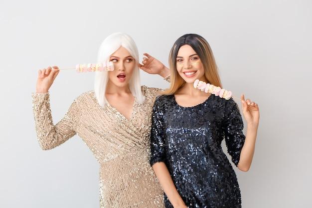 Belle giovani donne in parrucche e con marshmallow