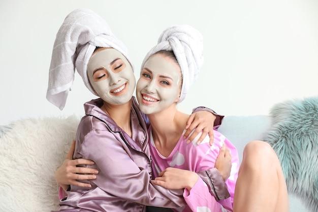 Belle giovani donne con maschere facciali a casa
