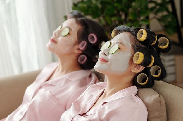 Belle giovani donne con rotoli di capelli che si rilassano sul divano con maschere idratanti e fette di pomodoro e cetriolo sui volti