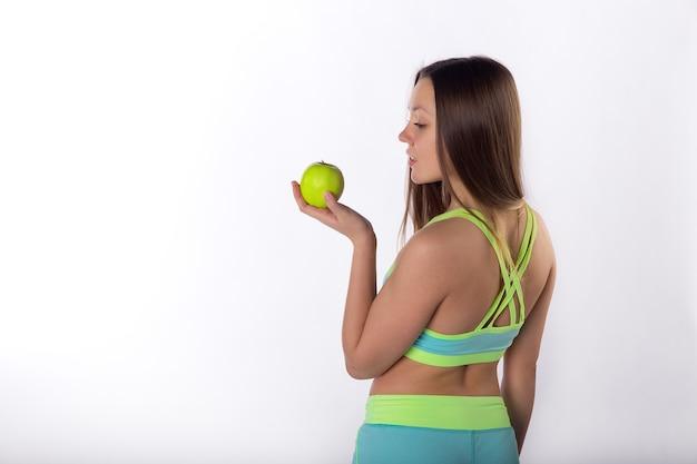 Bella donna fitness con mela in mano, sfondo bianco, vista posteriore. uno stile di vita sano. cura della salute con le vitamine