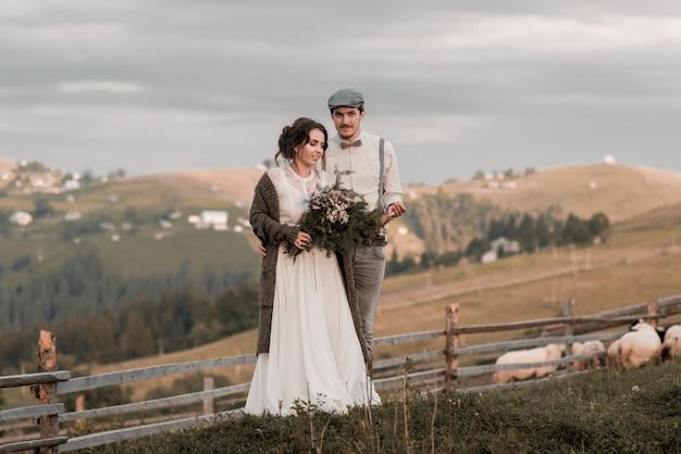 Bellissimi sposi in piedi vicino alla montagna con una vista perfetta