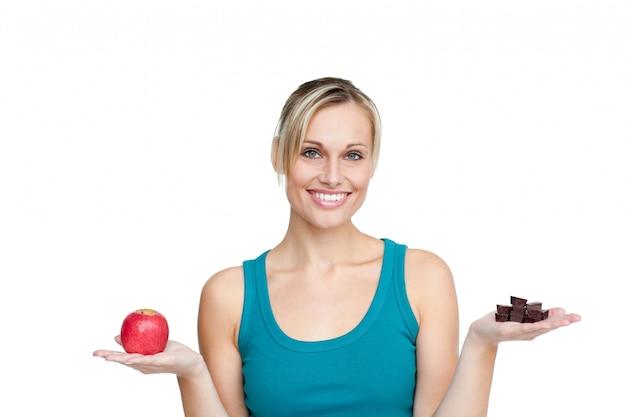 Bella donna che confronta mela con cioccolato