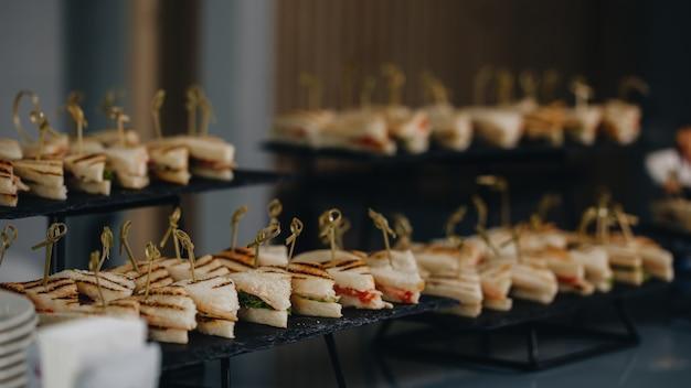 Tabella di banchetto di approvvigionamento meravigliosamente decorata con differenti spuntini e aperitivi dell'alimento con il panino