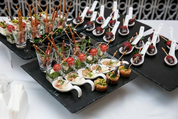 Tavolo per banchetti catering splendidamente decorato con diversi snack alimentari