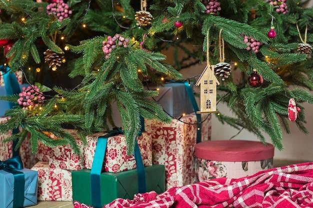 Albero di natale splendidamente decorato con molti regali sotto di esso nell'interno della casa decorata di capodanno.