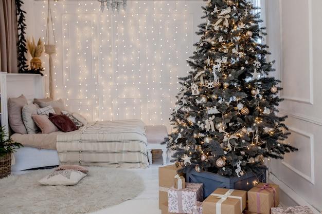 Albero di natale splendidamente decorato con molti regali sotto.