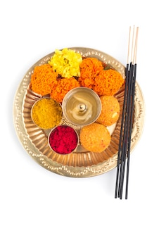Pooja thali splendidamente decorato per la celebrazione del festival da adorare, haldi o polvere di curcuma e kumkum, fiori, bastoncini profumati in lamiera di ottone, indù puja thali