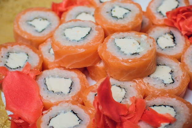 Il sushi splendidamente decorato su un piatto e le bacchette sono vicino ad esso. il sushi è il cibo tradizionale asiatico e giapponese. rotolo di sushi preparato con pesce crudo e un riso speciale. alimento sano di dieta.
