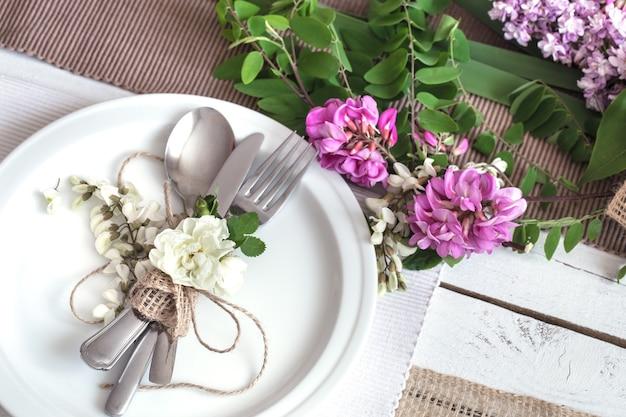 Tavolo decorato splendidamente ed elegante per le vacanze - matrimonio o san valentino con posate moderne, fiocco, vetro, candela e regalo