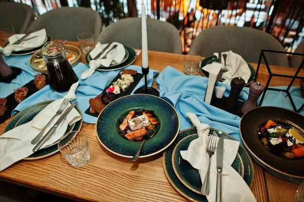 Tavoli splendidamente apparecchiati con cibo, bicchieri ed elettrodomestici nel ristorante.