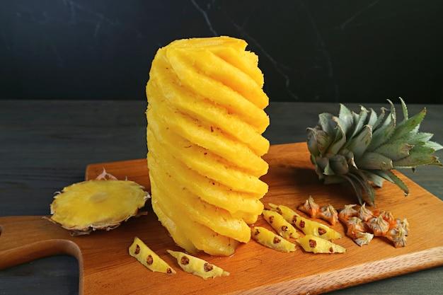 Splendidamente sbucciato e tagliato ananas maturo fresco su un tagliere di legno